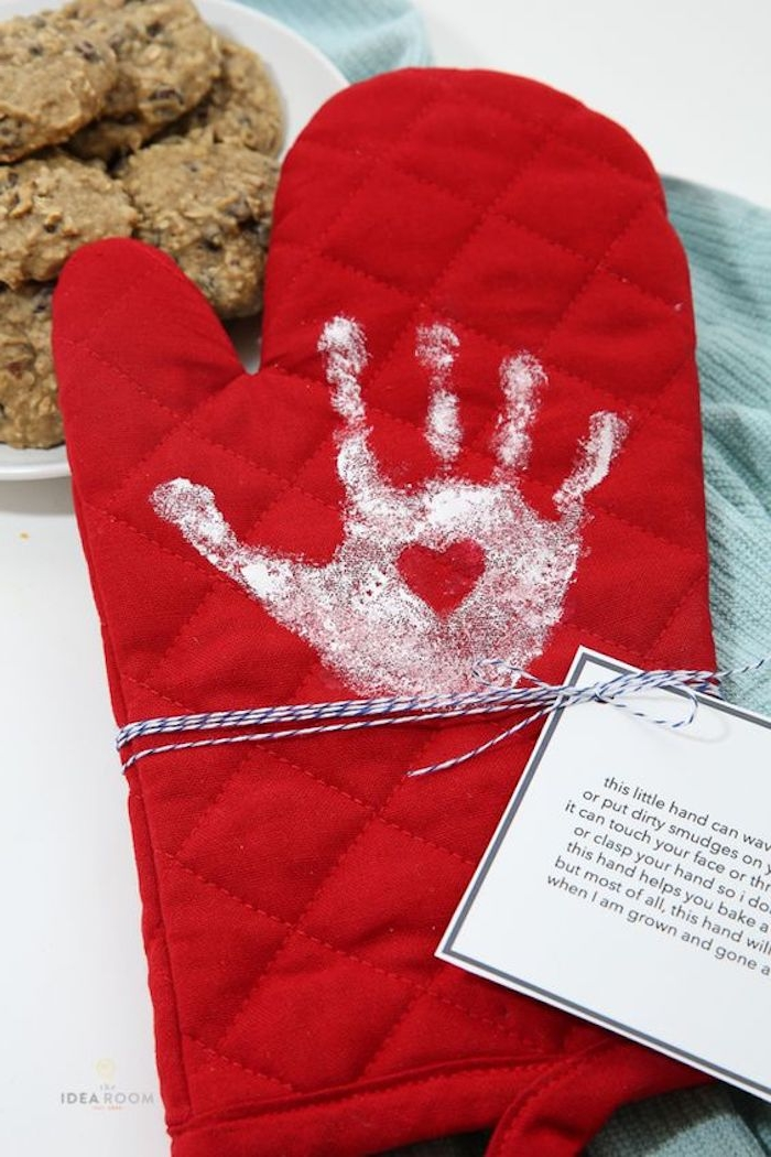 print of a small child's hand, with a little heart detail, on red oven mit, with thread and white label, mother's day gifts for grandma