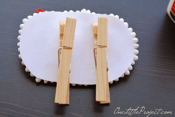 two plain wooden clothespins, stuck on the back of the lamb's paper body, craft ideas for kids, dark wooden surface