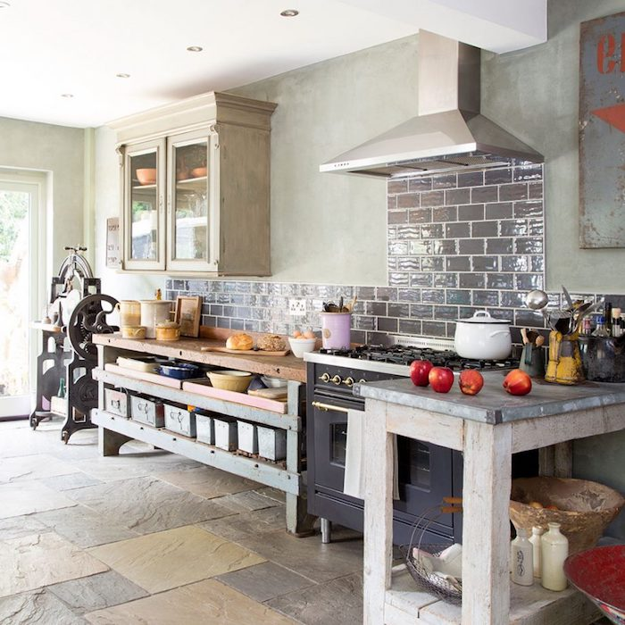 four red apples, on a wooden counter, with pale gray stone-like surface, country kitchen decorating ideas, in room with antique black stove, and shabby chic cabinets