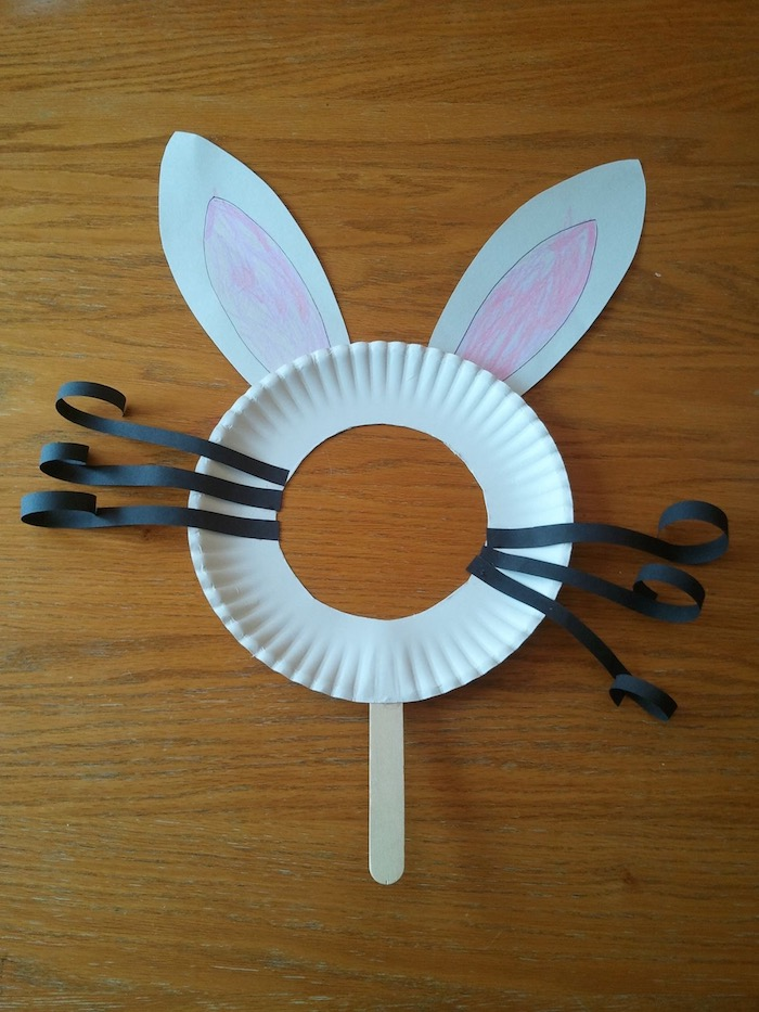 simple rabbit mask, made from white paper plate, with round hole, curled black paper whiskers, easter crafts for preschoolers, and hand-decorated ears, wooden ice cream stick holder