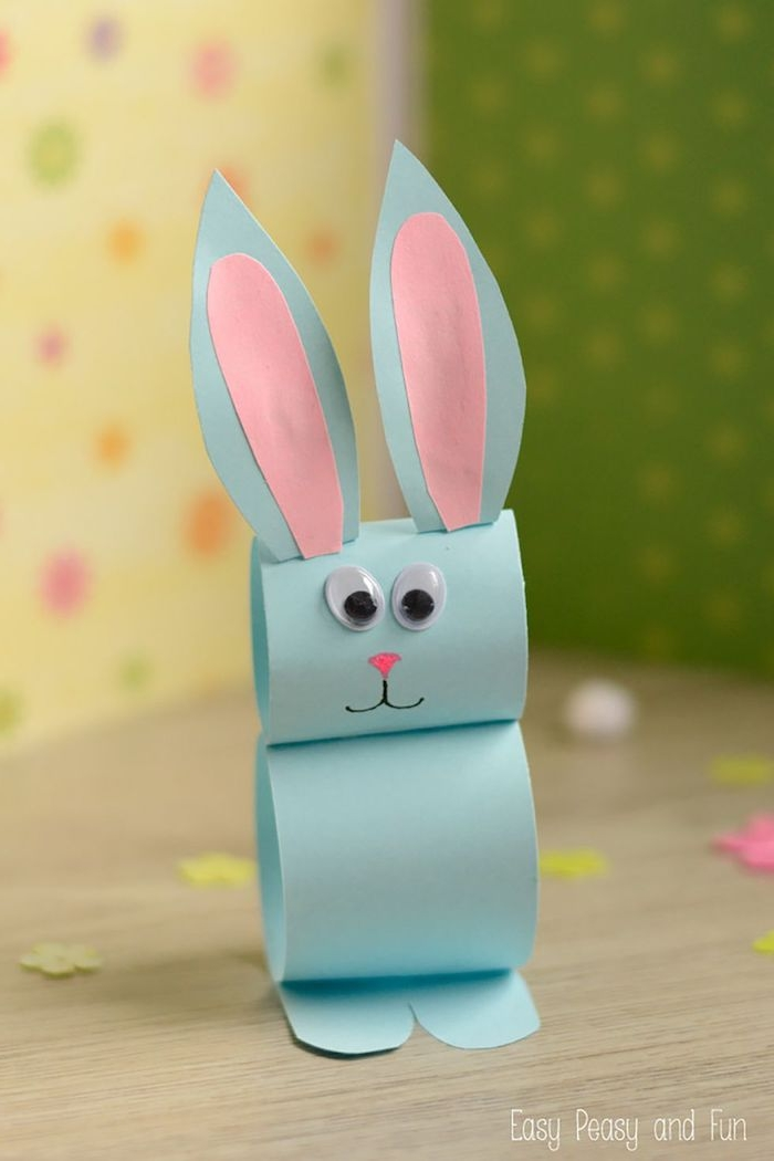 pale blue paper craft bunny, with pink ear details, googly eye stickers, and hand-drawn nose and mouth