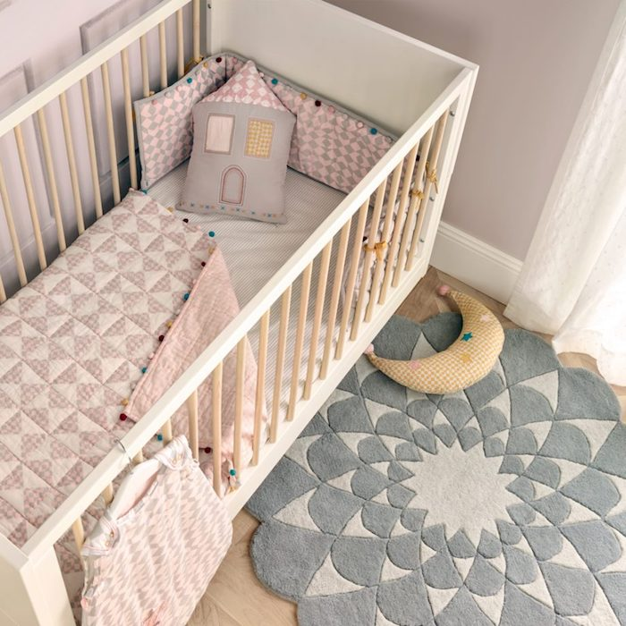 flower-shaped rug in two tones of gray, near white and beige baby crib, baby girl themes, pastel pink bedding, two stuffed toys