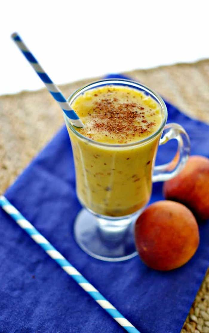 navy blue cloth, a straw and two peaches, clear glass with handle, containing yellow blended drink, dusted with brown powder, how to make a fruit smoothie