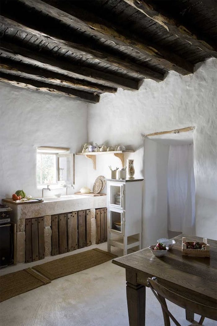 room with asymmetrical walls, covered in lime plaster, dark wooden ceiling with several large beams, country kitchen décor, antique sink near a small open window, dining table and chair