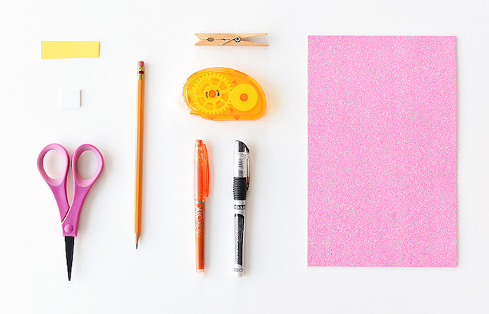 glittering pink card, near two pens, easter arts and crafts and materials, plain pencil and clothespin, sticky tape and scissors