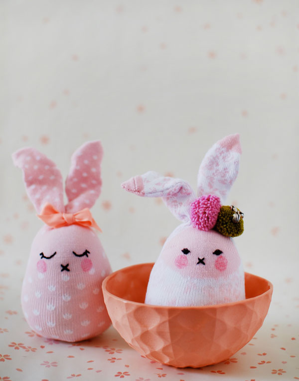 stuffed bunny dolls, made from two pink socks, with white pattern, black embroidered faces, easter crafts for kids, decorated with bow and pom poms