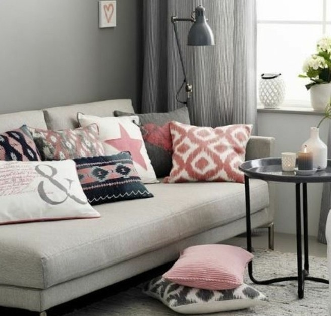 various cushions in pink, white and gray, on light gray sofa, near black metal coffee table, living room paint colors, grey walls and curtains
