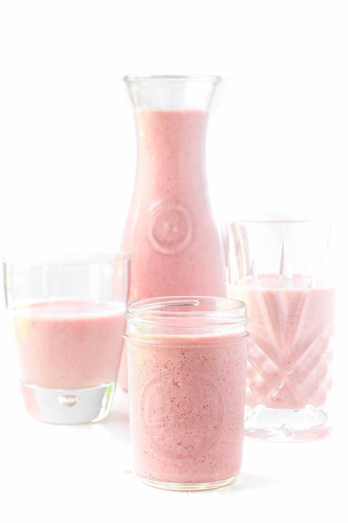 fruit smoothie recipes, simple pastel pink-colored strawberry smoothie, in pitcher and three glasses, on a pure white background
