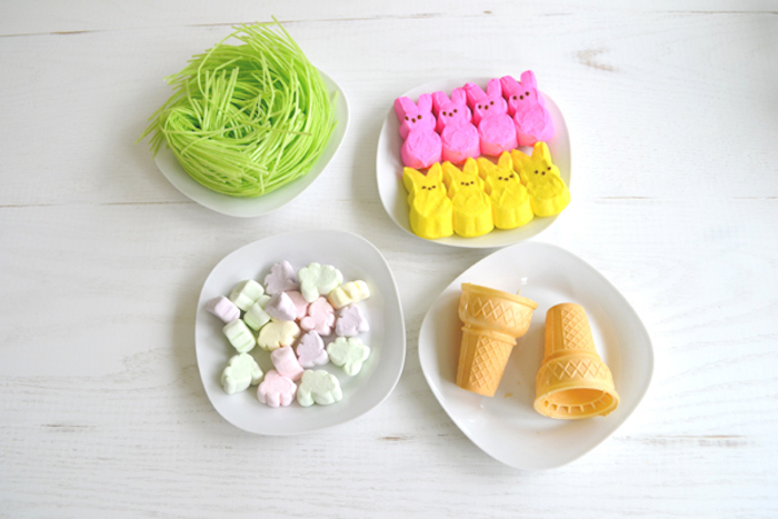 wafer ice cream cones, light green easter grass, eight pink and yellow bunny-shaped peeps, and some marshmallows, in four white plates
