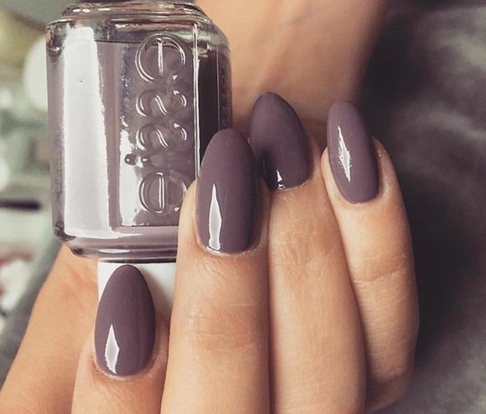 oval-shaped short stiletto nails, painted in plum colored nail polish, on hand holding nail polish bottle