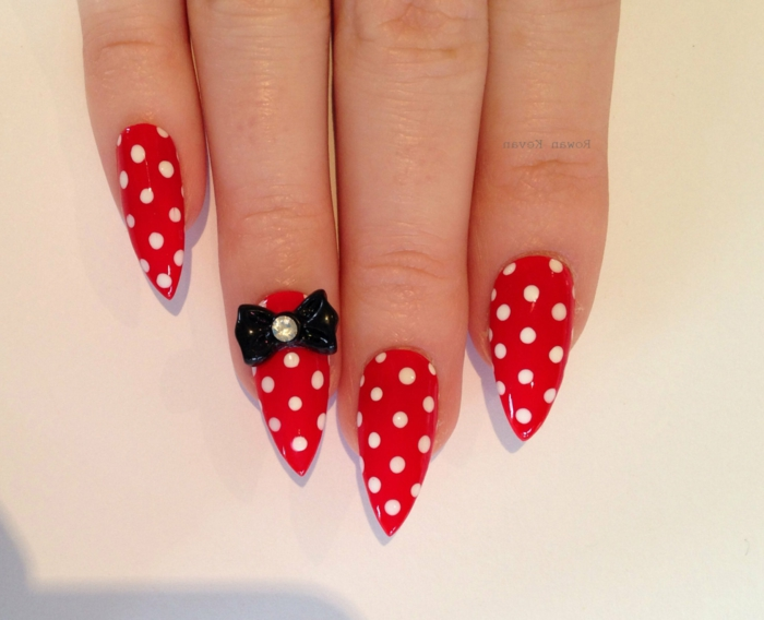 minnie mouse style nails, bright red with white polka dots, decorated with black, plastic bow-shaped sticker, long pointy manicure