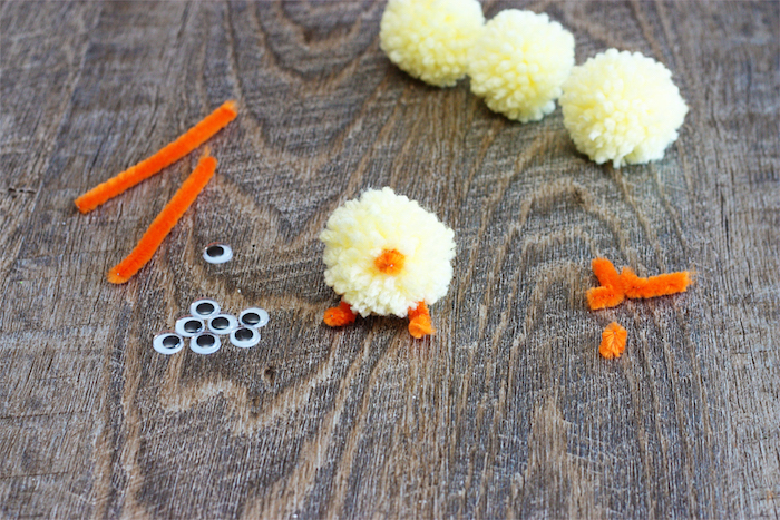 sticking orange fuzzy wire, on pale yellow pom pom, easter crafts for kids, supply of eye stickers , pom poms and fuzzy wire nearby