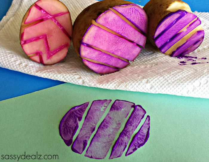 several stamps made from potatoes, shaped like easter eggs, with different carved patterns, easter crafts for preschoolers, covered in pink and purple paint, sheet of green paper with print nearby