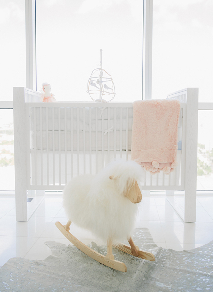 baby girl nursery ideas, fluffy rocking sheep toy, near pure white crib, with pale pink doll and blanket, light gray shiny tiled floor