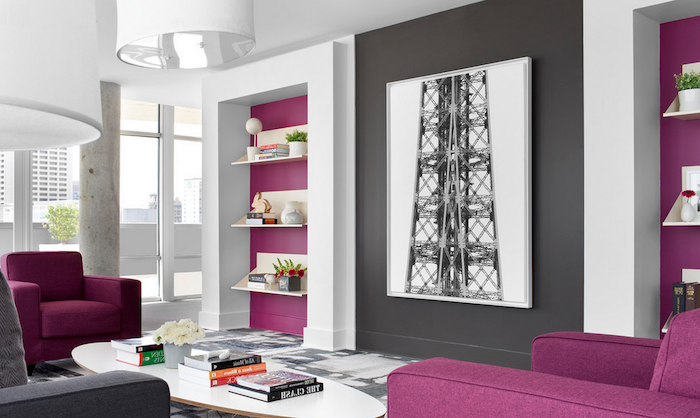 purple and dark gray details on white walls, in a large living room, with two purple armchairs, colors that go with gray walls, white oval coffee table, with several books and flowers