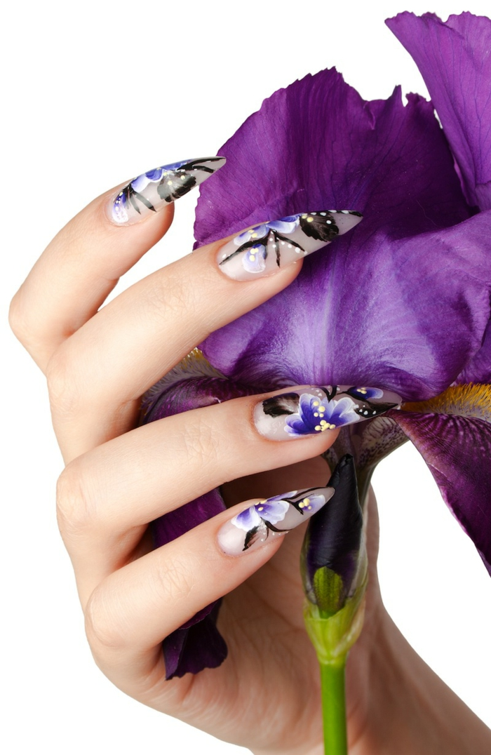 flowers in blue and black, yellow and , painted on long, matte acrylic nails, stilleto nail designs, on hand holding purple flower