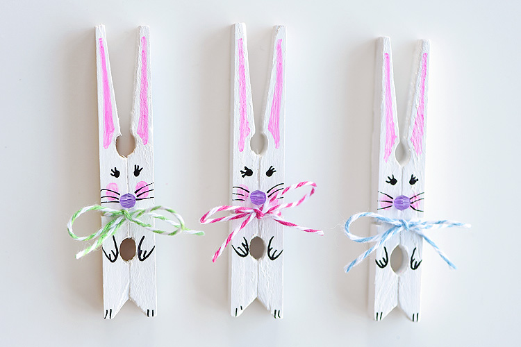 painted white clothespins, decorated to look like bunnies, easter crafts for adults, with bows made from two-tone thread
