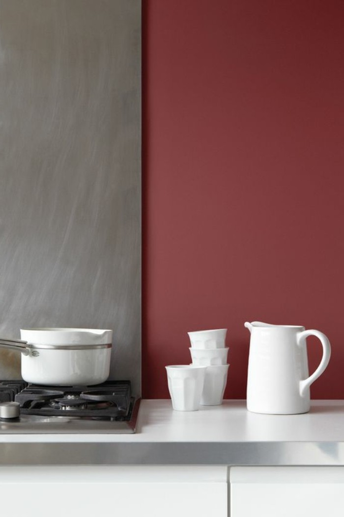 burgundy red and gray kitchen, with white cupboards and a stove, white jug with four matching ceramic cups