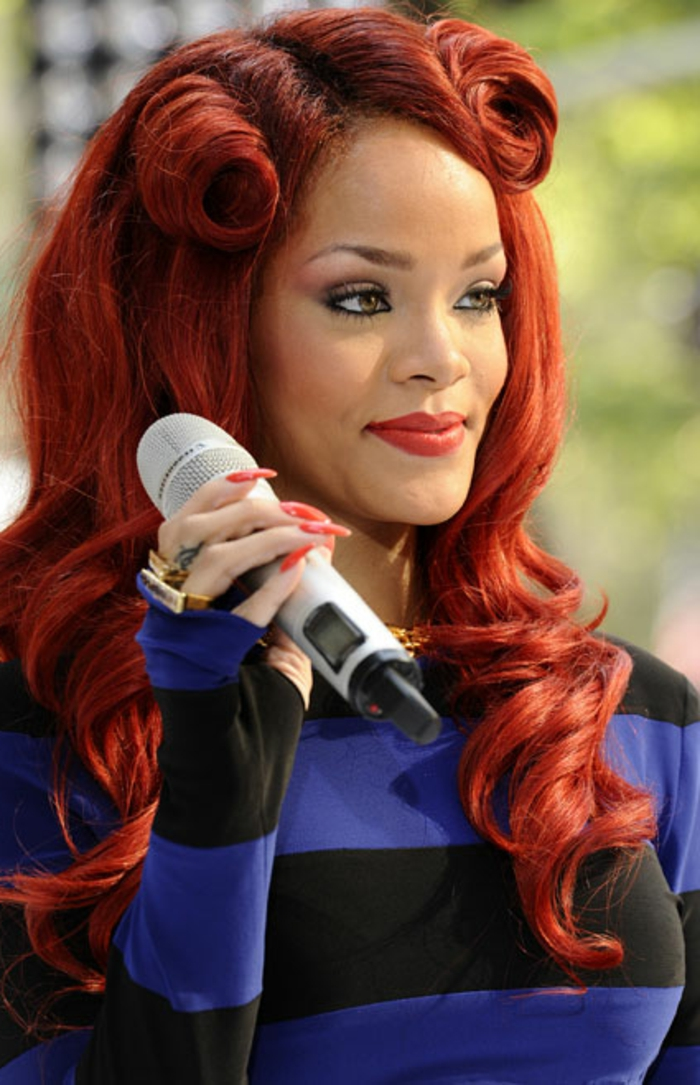 rihanna in blue and black striped top, sporting red dyed hair, with victory rolls and curls, wearing red nail polish, on long and sharp stiletto nails