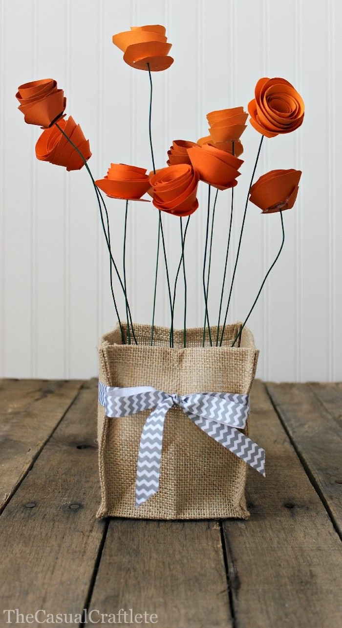 square burlap bag, decorated with grey and white ribbon, mothers day presents, containing eleven reddish paper flowers, with green wire stalks