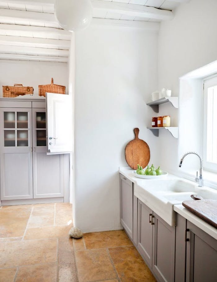 mink-colored cabinets, white sink with modern metal tap, inside bright kitchen, with white wall and ceiling, and beige stone floor, country kitchen decorating ideas
