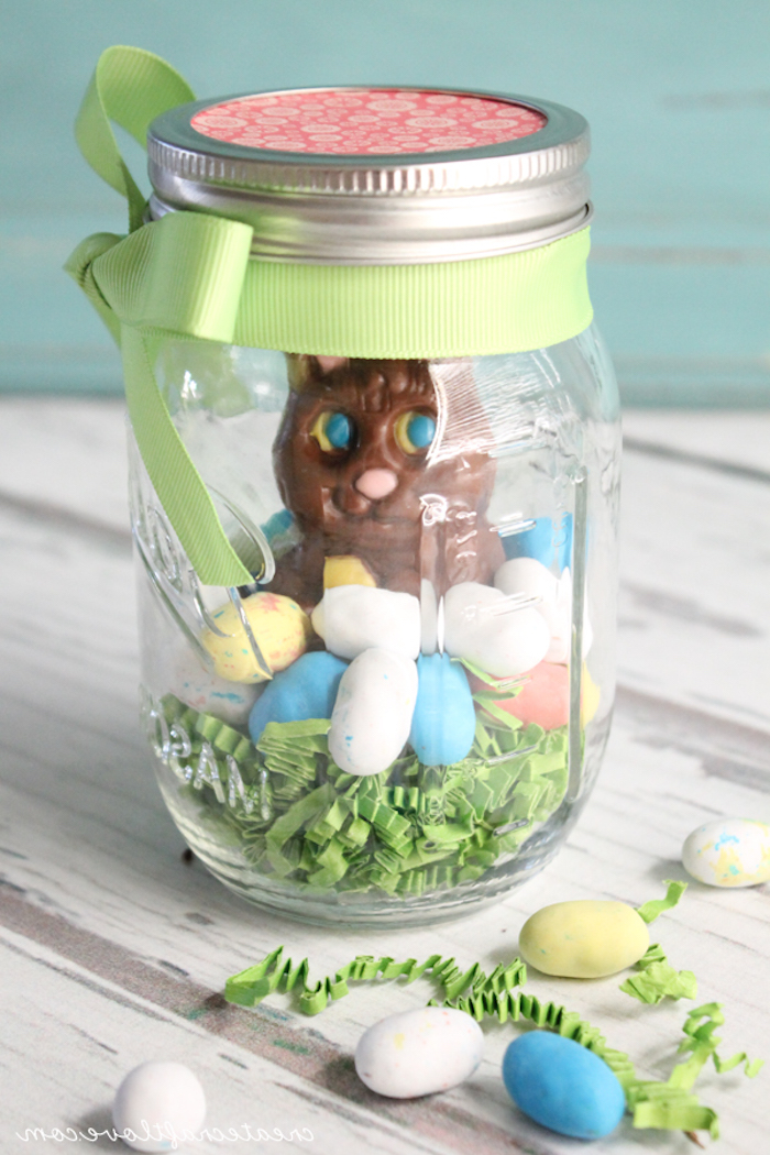 closed jar with pale green ribbon, tied in a bow, easter projects, containing pale green easter grass, multicolored egg-shaped candy, and a large chocolate bunny