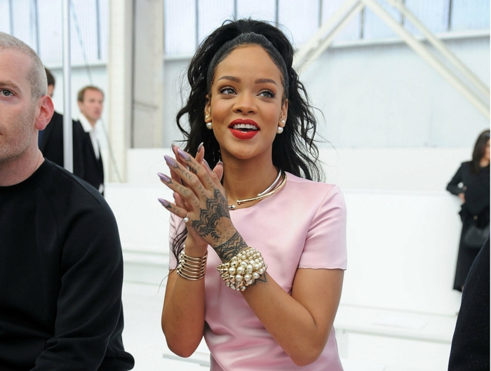 claping and smiling rihanna, in pale pastel pink t-shirt, with black wavy hair, lots of jewelry, henna hand tattoo, and stiletto nails, painted in pale pink