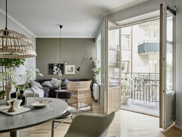 living room color ideas, bright and spacious room, with khaki-gray walls, navy blue sofa with grey cushions, pale grey table, open terrace