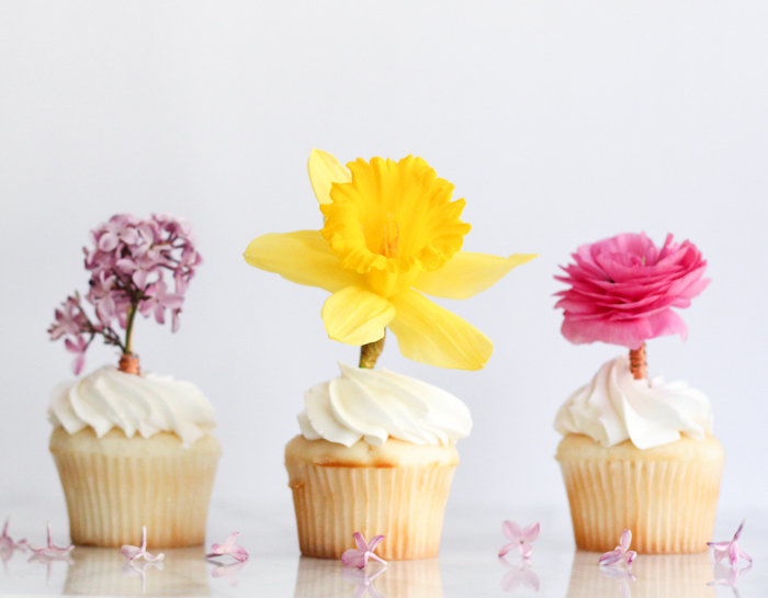 three cupcakes with white frosting, decorated with fresh flowers, lilac and daffodil, vibrant pink rose, mothers day gifts