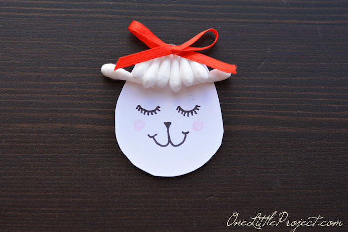 lamb's head, made from roundish piece of paper, decorated with hand-drawn face, cotton bud tips, and small red ribbon bow, craft ideas for kids