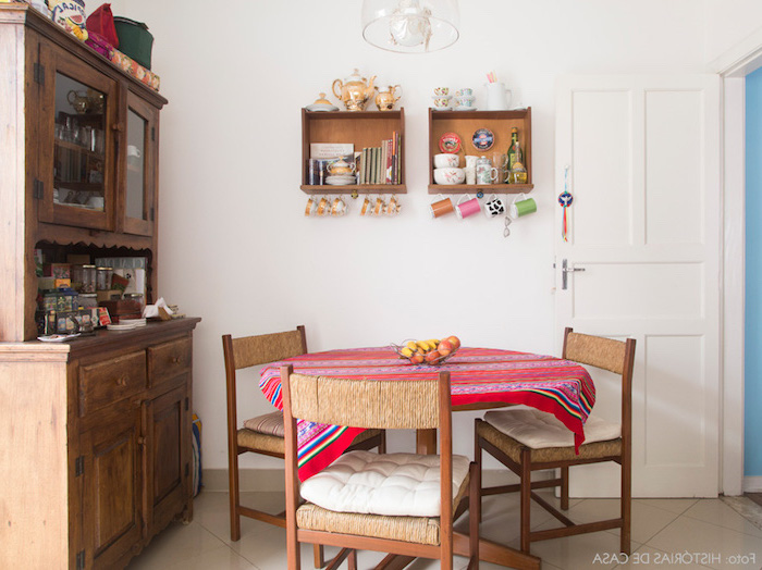 retro dining area, round wooden table, covered with red embroidered tablecloth, vintage wooden cupboard, country kitchen decorating ideas, white walls and beige floor