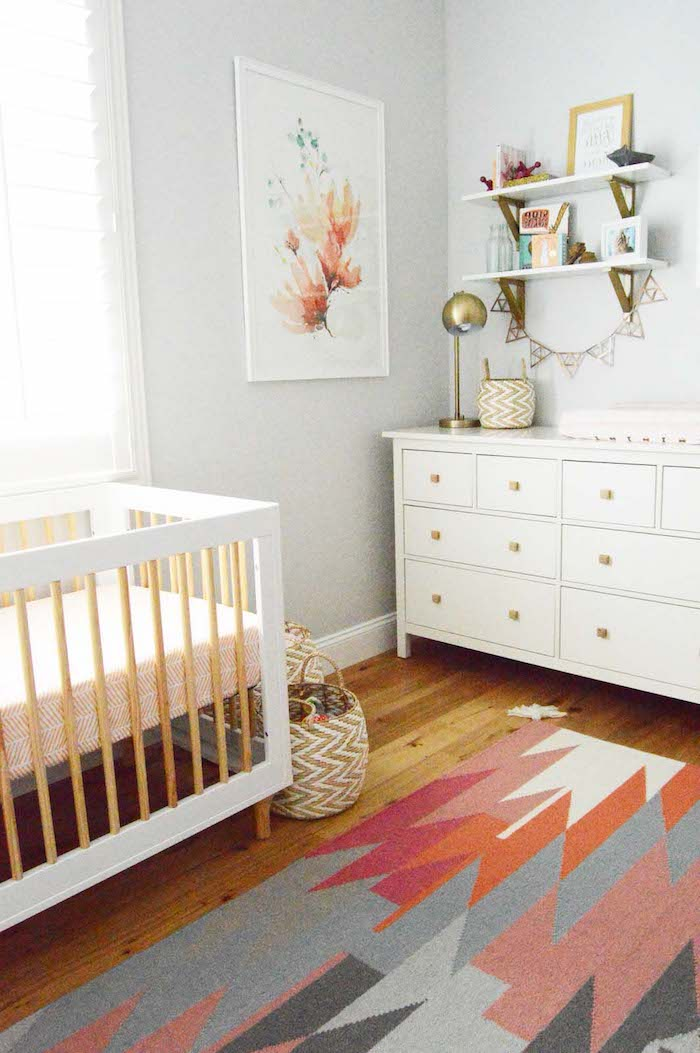 retro-inspired nursery ideas, white wooden crib, with beige details, matching chest of drawers, wooden laminate floor, and multicolored modern rug