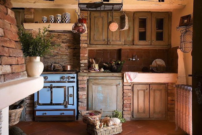 baskets with bread and other items, on a brown tiled floor, inside a kitchen with pale orange walls, and brick details, country kitchen decorating ideas, vintage wooden cupboards and an antique stove