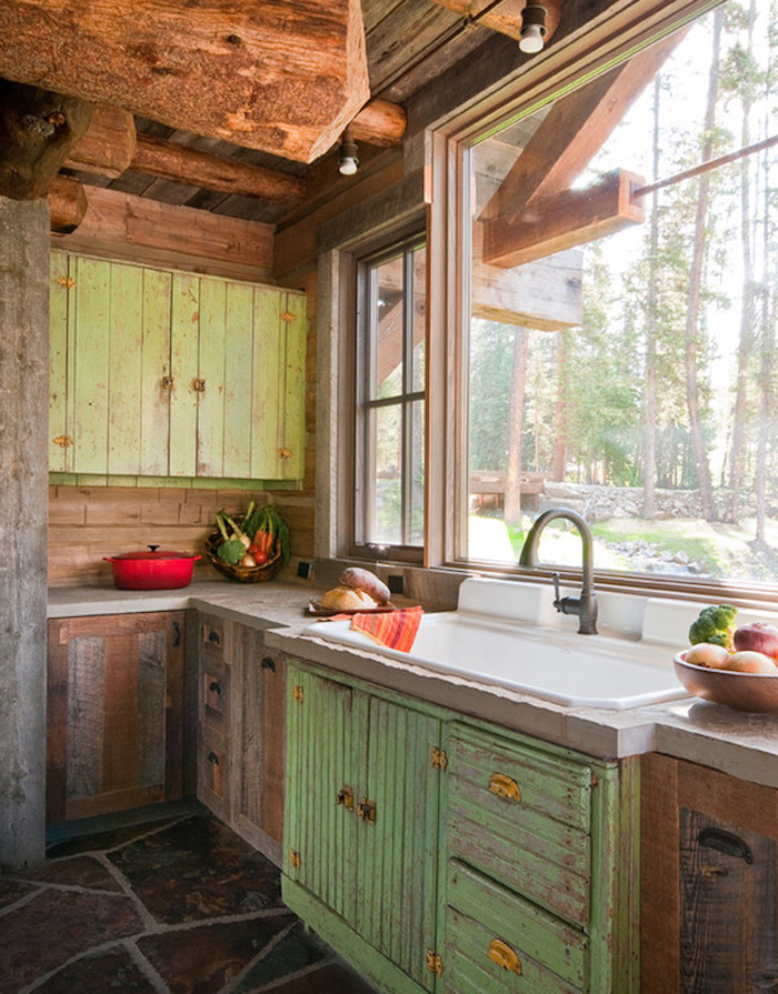 big window near a large sink, with antique metal tap, country kitchen decorating ideas, shabby green cabinets, and a stone floor