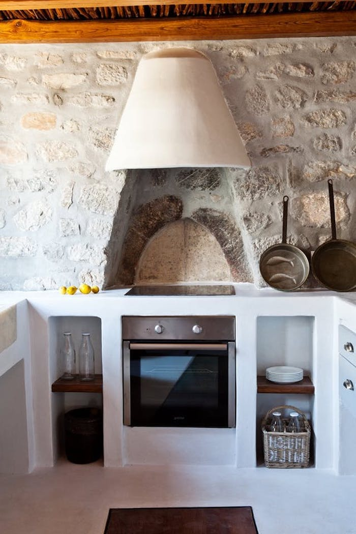 pans and bottles, in a kitchen with stone-covered walls, white lime plaster country kitchen cabinets, modern stove and wooden ceiling