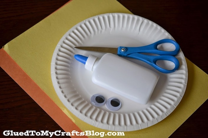 plastic glue bottle and scissors, googly eye stickers, inside white paper plate, placed on sheets of yellow, and orange card, easter crafts for preschoolers