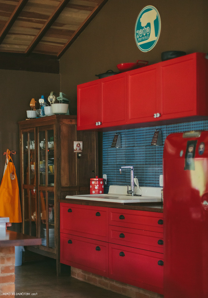 red country kitchen cabinets, near vintage dark brown wooden cupboard, in room with brown walls and floor