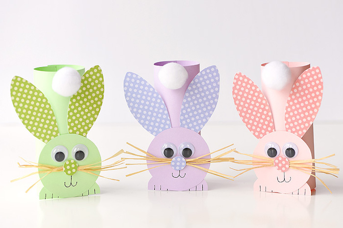 bunny ornaments, craft ideas for kids, made from pale green, pale purple and pale peach plain and patterned paper, decorated with eye stickers, faux straw whiskers, and cotton ball tails