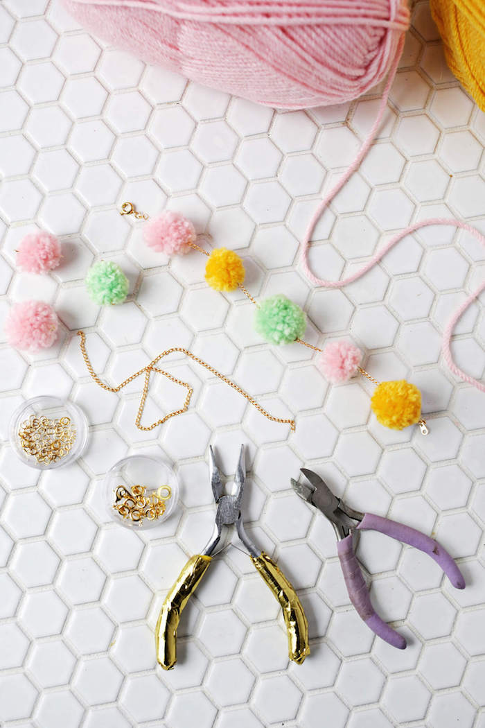 stringing pompoms together, on a thin golden chain, two pliers and jewelry making supplies, gift ideas for mom, pink and yellow woolen thread