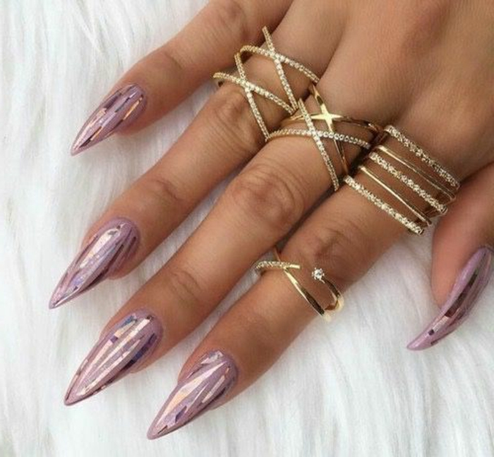 metallic-colored shards, on long stiletto nails, painted in rose ash pink nail polish, on hand with several rings