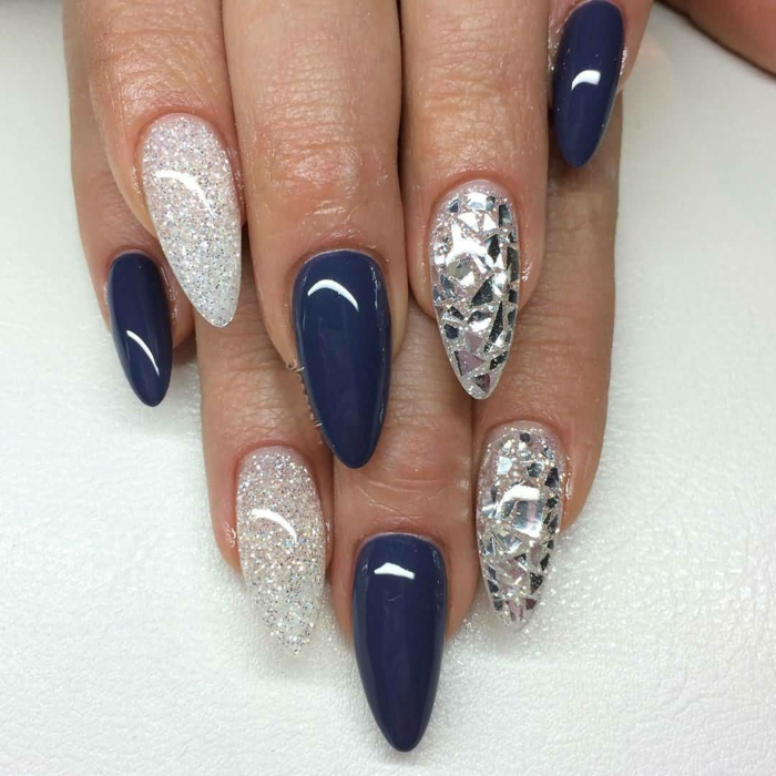 silver glitter and metallic shards, decorating stiletto acrylic nails, covered in dark blue, smooth and shiny nail polish