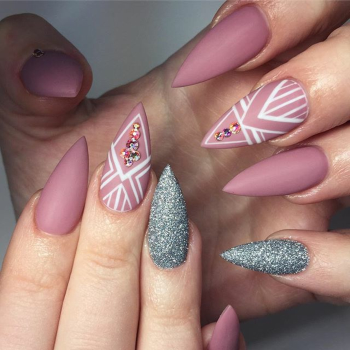 matte pink nail polish, with white decorations, and accent nails, covered in silver glitter, on two hands with long manicure, sharp stiletto nails