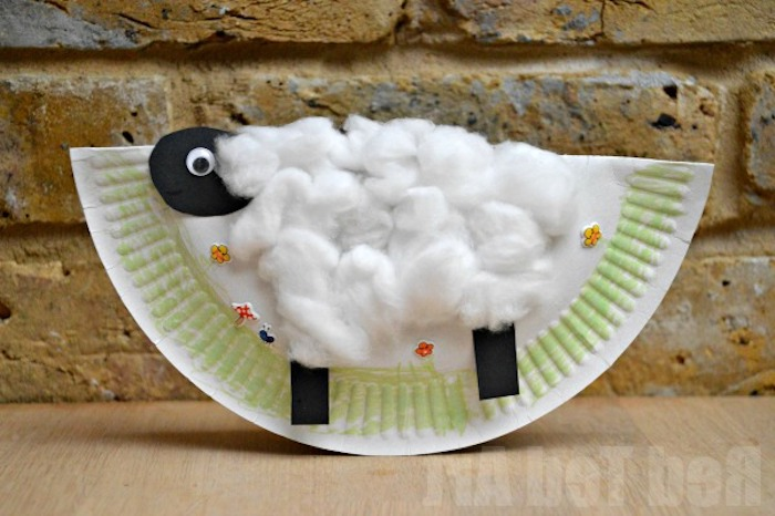 cotton covered collage of a sheep, with head and legs made from black paper, stuck on folded white paper plate, easter crafts for preschoolers, hand-drawn grass, and flower stickers