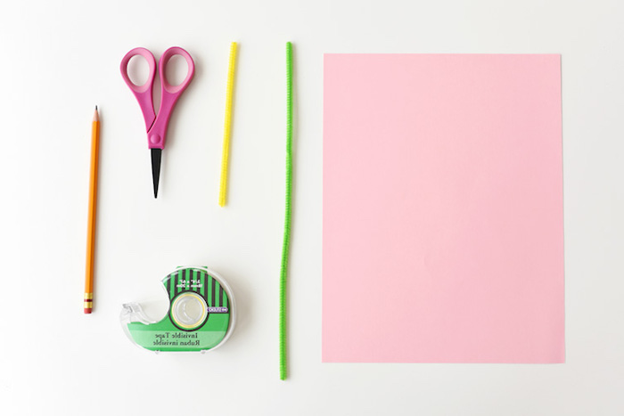 plain pencil and small pink scissors, green and yellow fuzzy wire, easter diy, sticky tape dispenser, sheet of pastel pink card