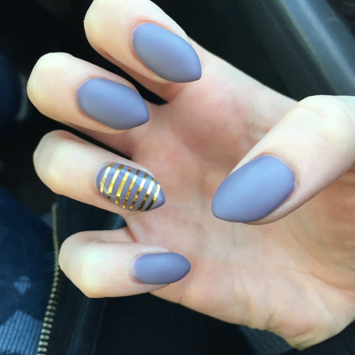 golden metallic stripes, on short but sharp stiletto nails, painted in grey, matte nail polish