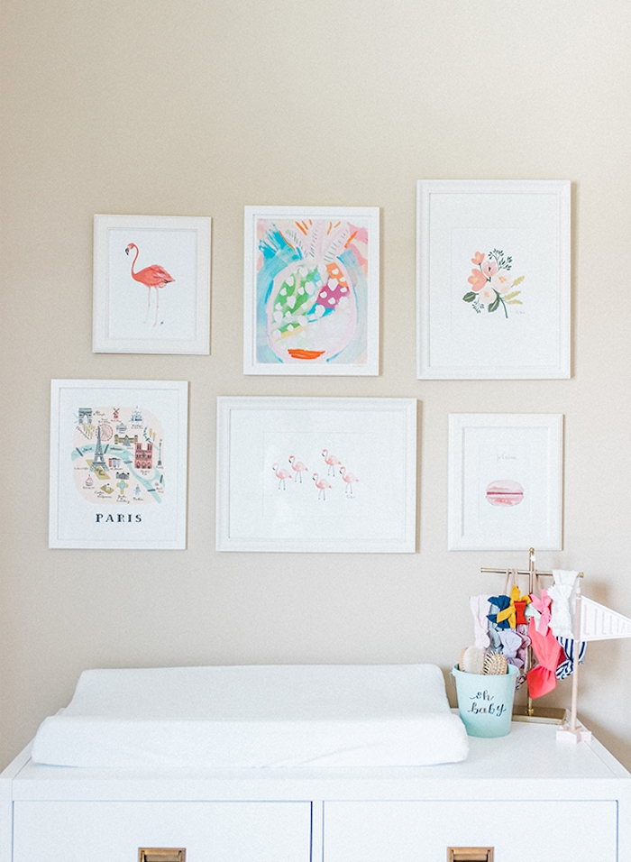 changing table in white, with small rack, holding many bows, and hairbands in different colors, baby girl themes, near six framed images, of pale pastel drawings