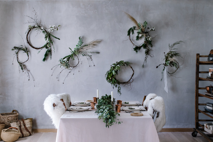 set table with white tablecloth, several wooden chairs, covered with lambskin throws, rustic country home décor, six decorative plant and flower wreaths, hung on a pale gray wall