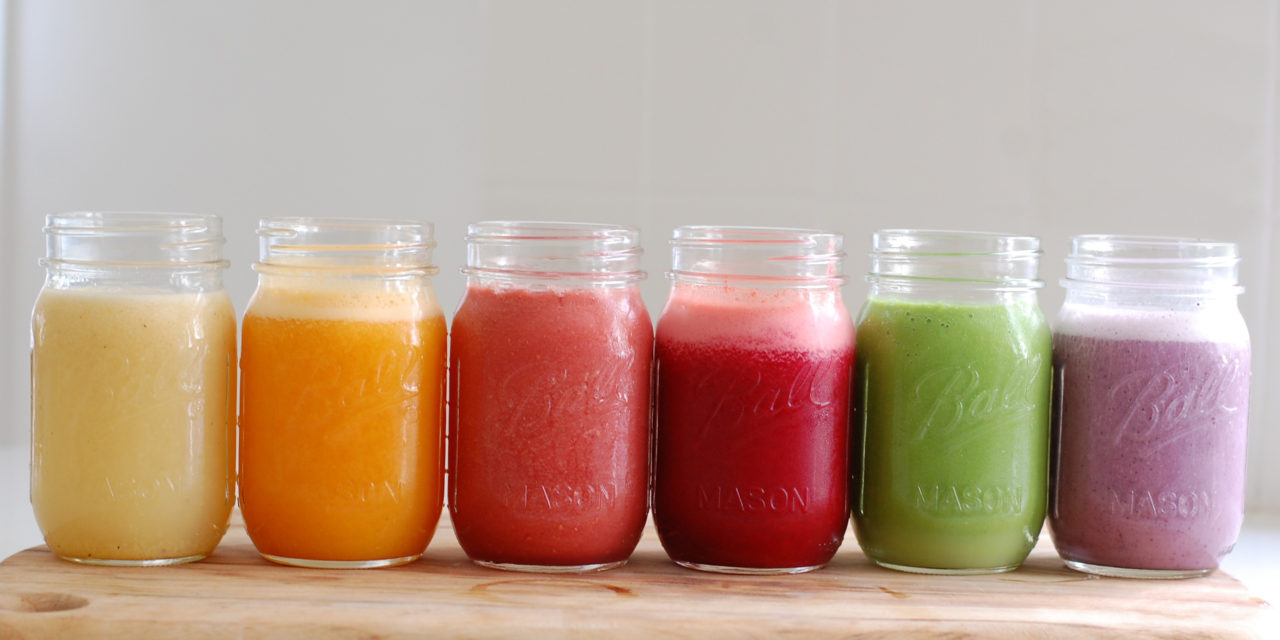 ball jars filled with blended fruit drinks, pale yellow and orange, pink and red, purple and green smoothie , on wooden surface