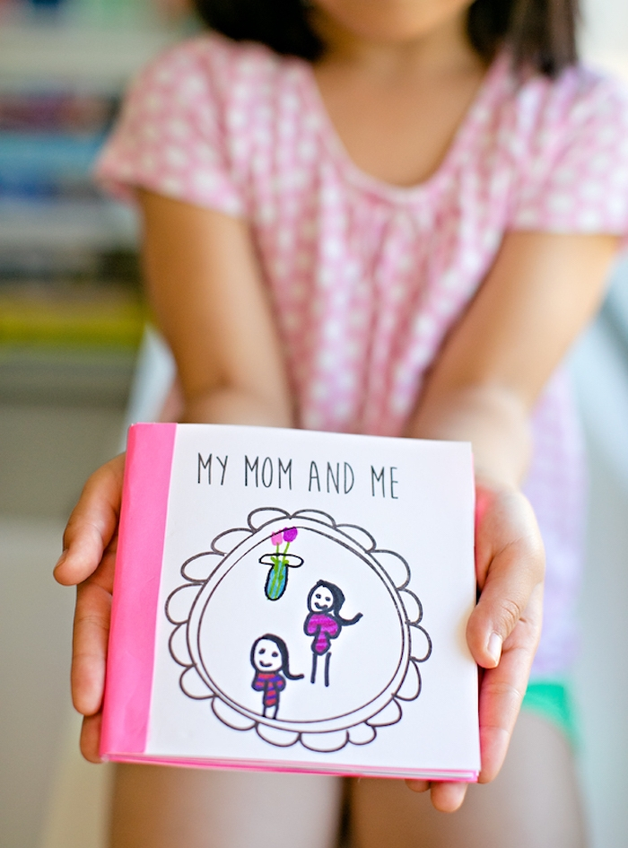 booklet in pink and white, with the title my mom and me, decorated with child's drawings, held by litte girl dressed in pink, top 10 mother's day gift ideas