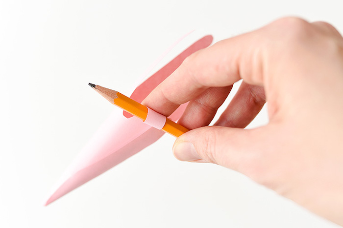 curling the folded, hand-shaped piece of paper, using a plain pencil, easter diy, fun activity for kids